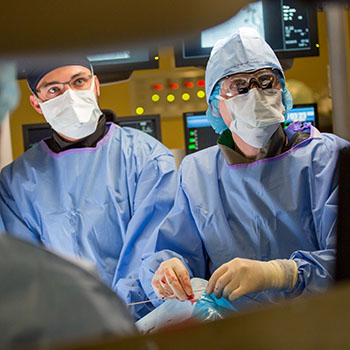 Dr. Thomas Lindsay performing life-saving aneurysm surgery