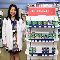 Pharmacist standing beside display of nicotine replacement products