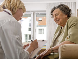 Image of a clinician with a clip board speaking with an older woman