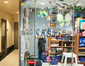 Magic Castle childcare centre with stickers on the window and toys and books inside the play area