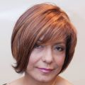 Female cancer survivor wearing short, red, human hair wig with bangs
