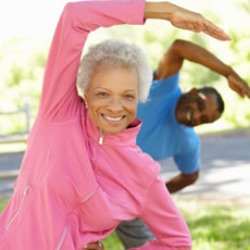 Older woman raising arm over head in exercise, with younger man behind her doing the same exercise