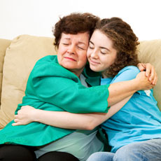 Young girl hugging middle aged woman on a couch