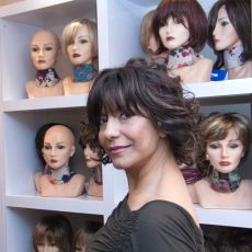Female cancer survivor wearing wig, standing in front of wall of mannequins displaying wigs