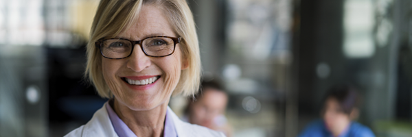 smiling blond woman in labcoat with glasses