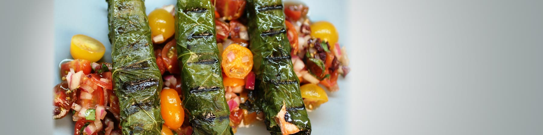 Grilled fish wrapped in grape leaves