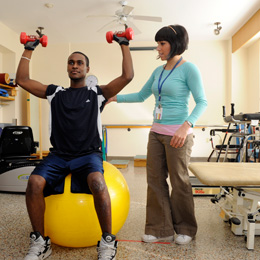 Picture of a patient on a bouncy ball lefting weights