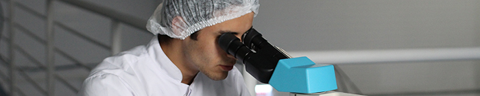 close-up of man looking through microscope