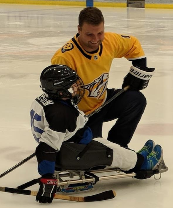 Cody on ice with child with disabilities