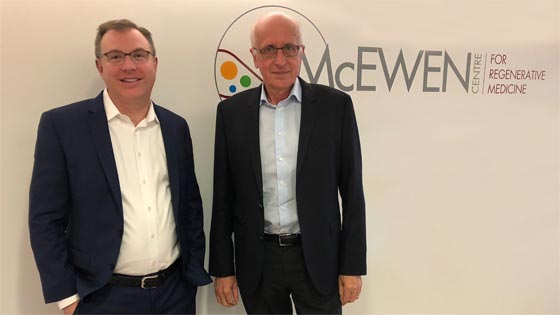 Pair standing in front of McEwen Centre sign