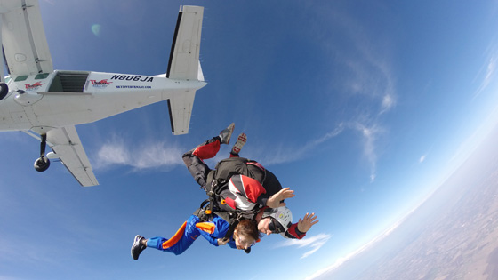 Woman and skydiving instructor jumping out of plane