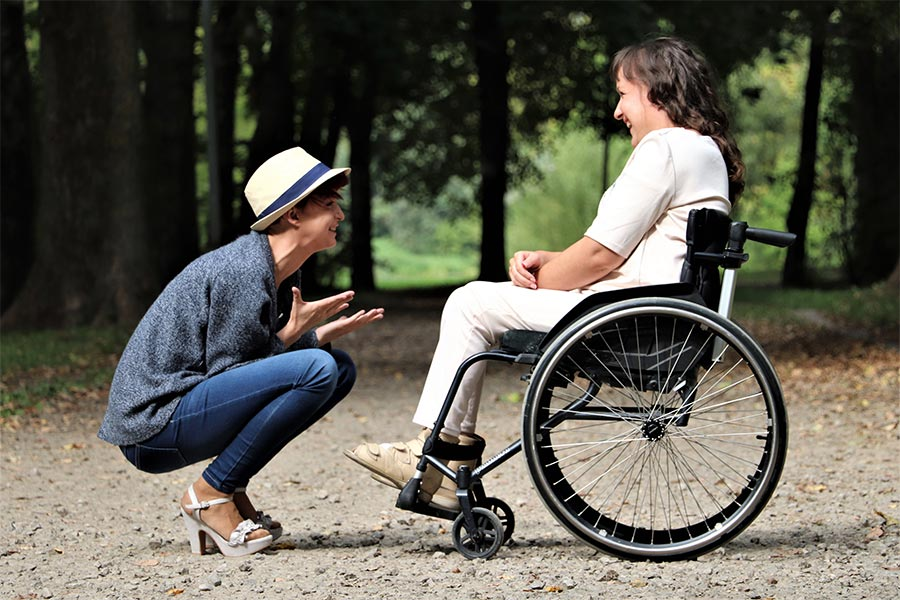 Woman talking to another woman in a wheelchair