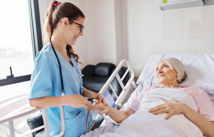 Nurse holding hand of woman in bed