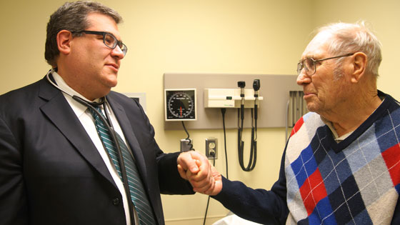Image of Dr. Eric Horlick holding hands with patient, David McCallum